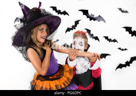Kids celebrate Halloween in costumes of witch and vampire. Vampire pretends to bite witch's arm and she smiles in response. - Stock Photo