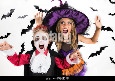 Trick or Treat! Kids scare people in Halloween night to earn candies according to the holiday tradition - Stock Photo
