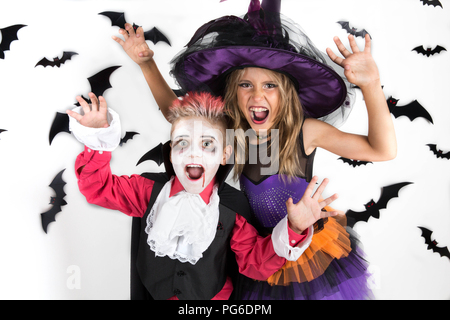 Halloween kids, Happy scary girl and boy dressed up in halloween costumes of witch, sorcerer and vampire, Dracula for halloween party, pumpkin patch - Stock Photo