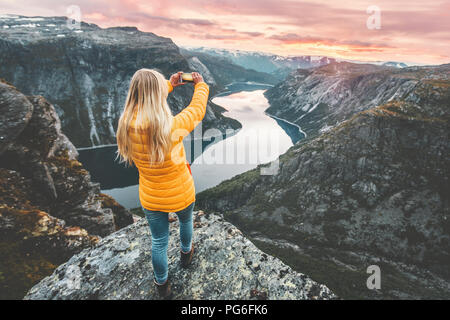 Woman taking photo by smartphone on mountain cliff over lake traveling in Norway adventure lifestyle active vacations modern technology connection con - Stock Photo