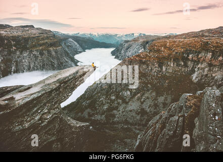 Traveler man sitting alone on the edge of Trolltunga cliff traveling in Norway adventure lifestyle extreme trip vacations outdoor mountains over cloud - Stock Photo