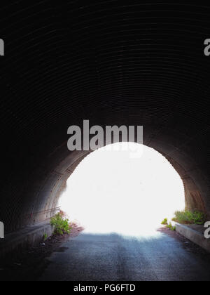 Dark corrugated tunnel and road leading under a French Motorway Autoroute - Stock Photo