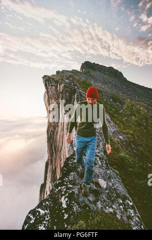 Man walking alone on the edge mountain ridge above clouds travel adventure lifestyle extreme hiking vacations - Stock Photo