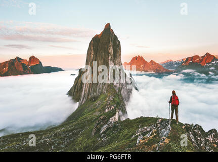 Traveler hiking on mountains ridge over clouds adventure journey traveling outdoor in Norway active vacations sunset Segla mountain - Stock Photo