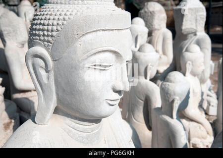 Close up of a white marble Buddha statue head with more white marble Buddha statues in the background Mandalay Myanmar - Stock Photo