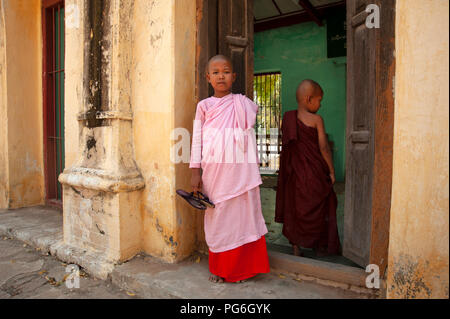 Very young girl Buddhist nun wearing pink and small Buddhist novice boy monk standing in the entrance to a run down temple building in Bagan Myanmar - Stock Photo
