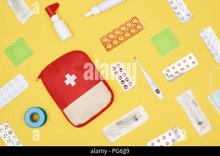 top view of first aid kit with various medicines isolated on yellow - Stock Photo