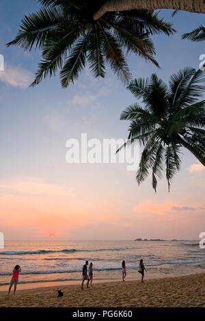 Vertical view along the coast at sunset in Hikkaduwa, Sri Lanka. - Stock Photo