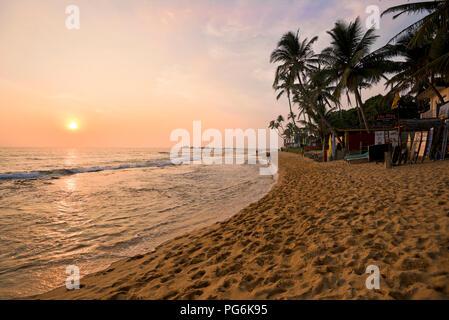 Horizontal view of the beach at sunset in Hikkaduwa, Sri Lanka. - Stock Photo
