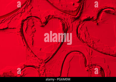 elevated view of shapes of cookie cutters in shape of hearts on red powder - Stock Photo