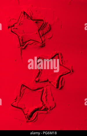 elevated view of shapes of cookie cutters in shape of stars on red powder - Stock Photo