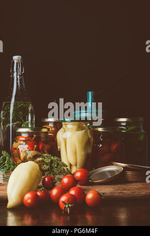 glass jars with preserved vegetables and fresh vegetables on table - Stock Photo