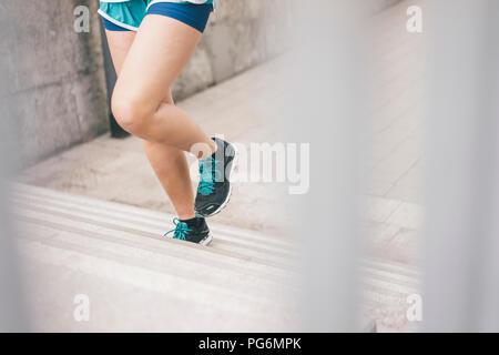 Close-up of woman running upstairs - Stock Photo