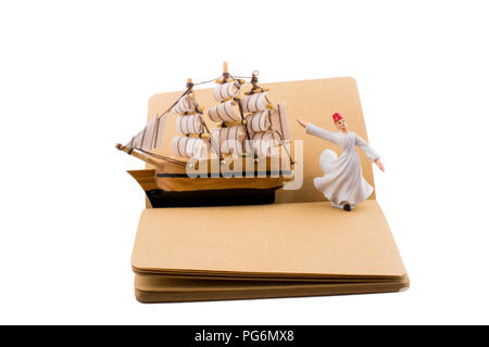 Sufi Dervish and a ship on a notebook on white background - Stock Photo