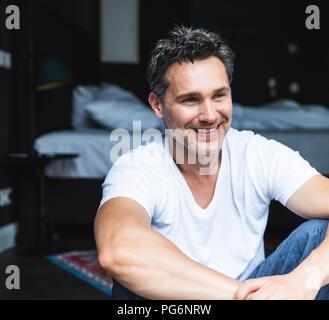 Smiling man in pyjama at home sitting down