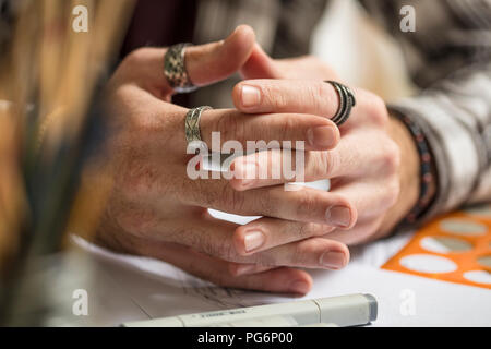 Close-up of artist's hands resting on table - Stock Photo