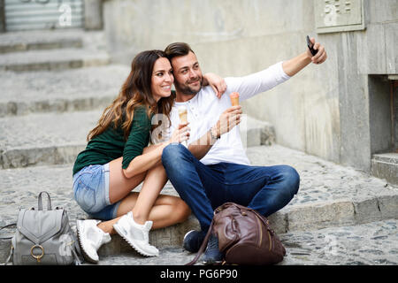 Tourist couple with ice cream cones in the city taking a selfie - Stock Photo