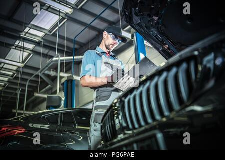 Caucasian Car Mechanic in His 30s Performing Vehicle Maintenance with Documentation in Hand. - Stock Photo