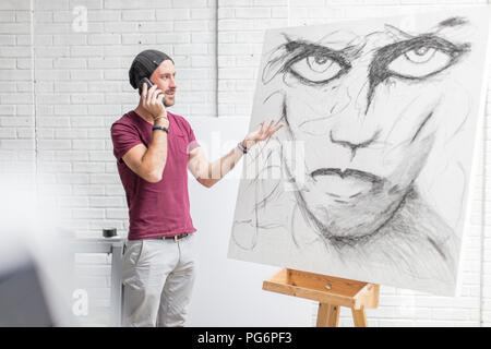 Artist on the phone in studio next to drawing - Stock Photo