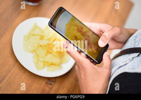 Woman's hands taking photo of potato chips with cell phone, close-up - Stock Photo