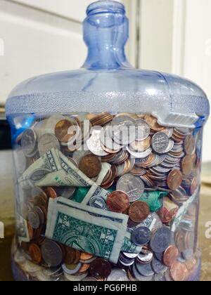 Two-gallon water bottle filled with assorted US coins, a couple dollar bills. - Stock Photo