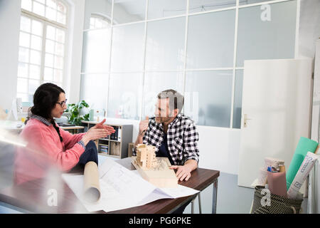 Colleagues discussing architectural model in office - Stock Photo