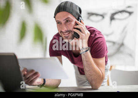 Artist using tablet and cell phone in studio - Stock Photo