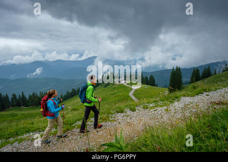 Germany, Lenggries, young couple with hiking poles hiking upwards - Stock Photo
