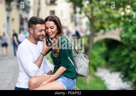 Happy tourist couple using cell phone in the city - Stock Photo