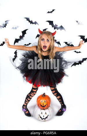 Little Girl with a demon devil costume dressed up in black red dress and red devil horns  for pumpkin patch and halloween party, posing with happy smi - Stock Photo