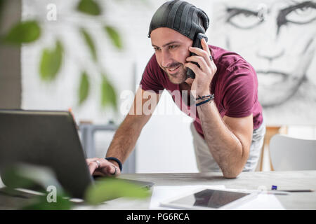 Artist using laptop and cell phone in studio - Stock Photo