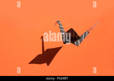 Origami crane, orange background, shadow, copy space - Stock Photo