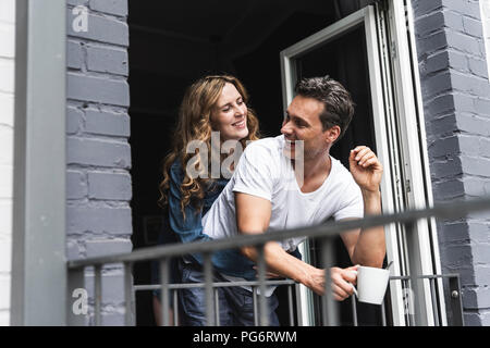 Happy couple in nightwear at home at balcony door - Stock Photo