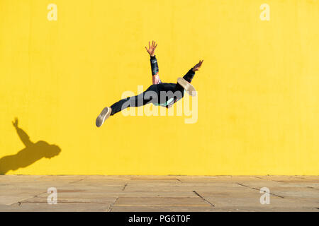 Acrobat jumping somersaults in front of yellow wall - Stock Photo