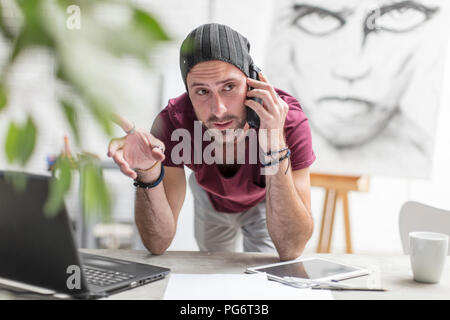 Artist on cell phone in studio - Stock Photo