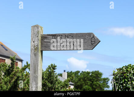 A wooden footpath finger post saying Coast Path , public footpath to Porthcurno 1/4 miles, Cornwall, England - Stock Photo