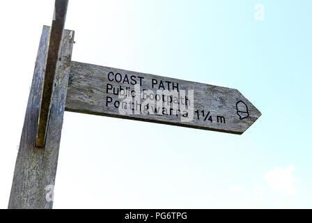 A wooden footpath finger post saying Coast Path , public footpath to Porthgwarra 1 1/4 miles, Cornwall, England - Stock Photo