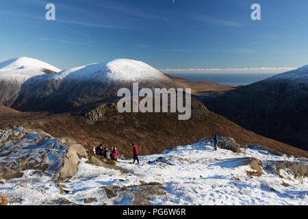 Group of winter hillwalkers enjoying a rest on Doan mountain. Views to Ben Crom directly in front and snowcapped Lamagan behind. Slieve Donard on left. - Stock Photo