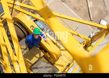 Construction worker standing on crane - Stock Photo