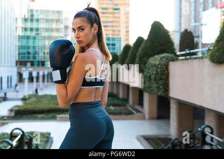 Portrait of sportive young woman wearing boxing gloves in the city - Stock Photo