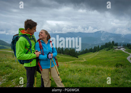 Germany, Lenggries, happy young couple with hiking poles and backpacks on Alpine meadow - Stock Photo