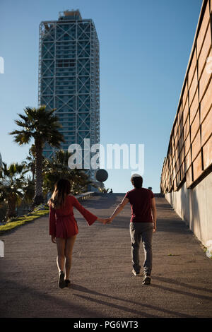 Spain, Barcelona, couple walking hand in hand  in the city - Stock Photo
