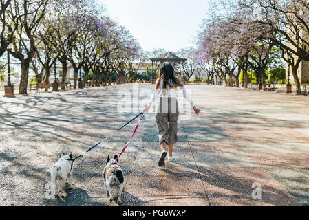 Spain, Andalusia, Jerez de la Frontera, Woman running with two dogs on square - Stock Photo