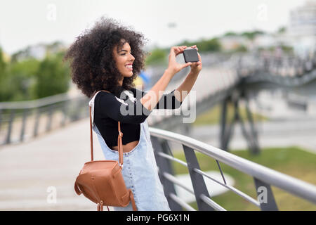 Smiling young woman with brown leather backpack standing on a bridge  taking photos with smartphone - Stock Photo