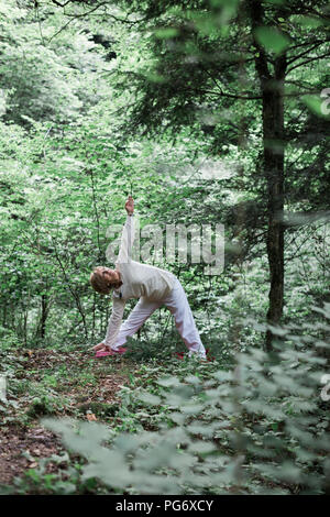 Senior woman doing yoga in the forest, triangle pose - Stock Photo