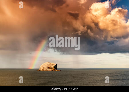 UK, Scotland, East Lothian, North Berwick, Firth of Forth, view of Bass Rock (world famous Gannet Colony) with rainbow and storm clouds - Stock Photo
