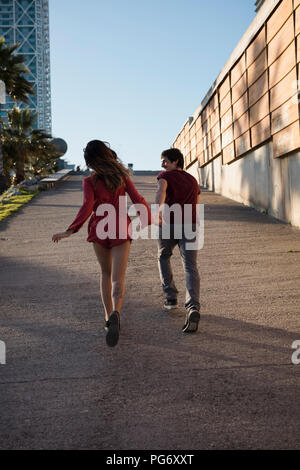 Spain, Barcelona, couple running hand in hand  in the city - Stock Photo