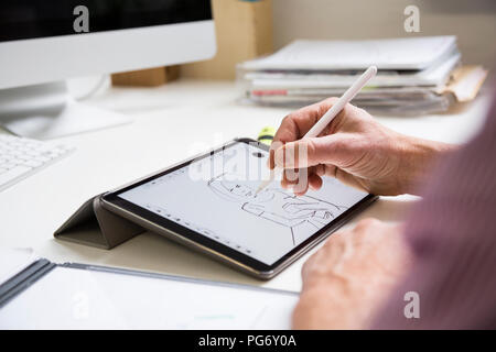 Close-up of man working at desk in office drawing female figure on tablet - Stock Photo