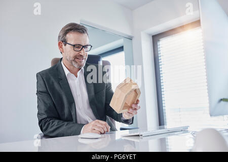 Smiling businessman at desk in office looking at architectural model - Stock Photo