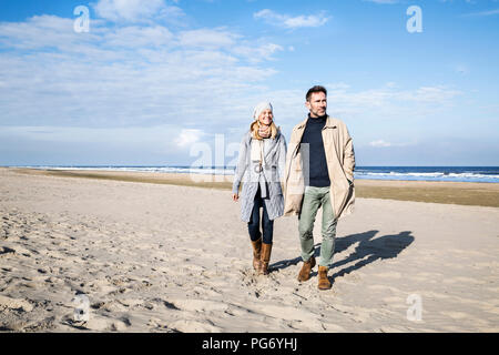 Couple in warm clothing walking on the beach - Stock Photo